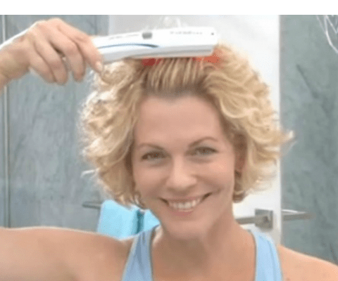 woman using hairmax laser comb